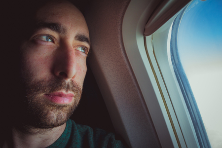 Close up of a pensive man looking outside through the window of an airplane.