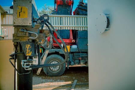 Closeup of hydraulic pistons of a parking rigging truck with heavy lifting crane arm machine. It is parked near a residential or industrial area with an emergency bomb shelter in Sderot, Israel.