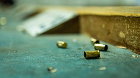 Empty pistol bullet shells on wooden table in a shooting range. Extreme close up and selective focus with blur background.