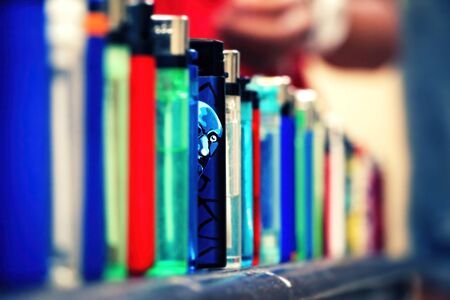 Lighters lined up. One blue color lighter stands out from the rest. Man's face Illustrated on it and it looks like he glances out to the camera. Closeup, selective focus with copy space.