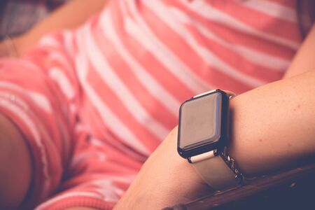 Smartwatch on sitting young woman hand. Close up, selective focus with copy space. Stock Photo