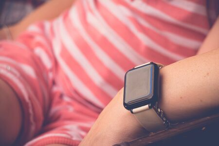 Smartwatch on sitting young woman hand. Close up, selective focus with copy space. 版權商用圖片