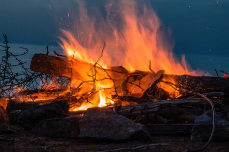 Campfire at twilight on the beach. Close up on the fire with sparks and heatwave. Stock Photo