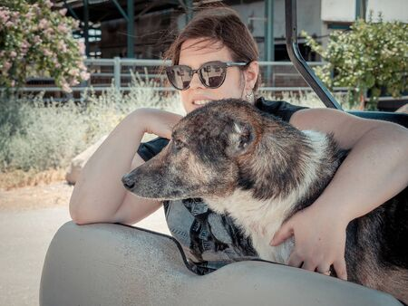 Caucasian woman is holding her dog while traveling. They riding in an electric golf cart in the nature of northern Israel on summer sunny day. Mixed breed dog with cropped ears.