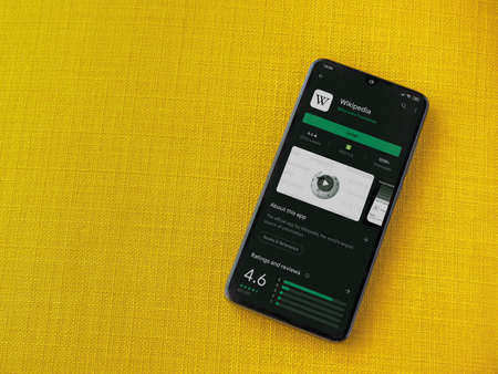 Lod, Israel - July 8, 2020: Wikipedia app play store page on the display of a black mobile smartphone on a yellow fabric background. Top view flat lay with copy space.
