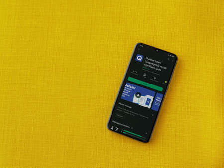Lod, Israel - July 8, 2020: Quizlet - Language learning app play store page on the display of a black mobile smartphone on a yellow fabric background. Top view flat lay with copy space.