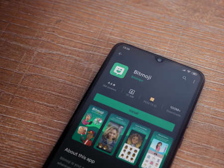 Lod, Israel - July 8, 2020: Botmoji app play store page on the display of a black mobile smartphone on wooden background. Top view flat lay with copy space.