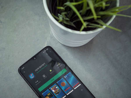 Lod, Israel - July 8, 2020: Modern minimalist office workspace with black mobile smartphone with Domino's Pizza Israel app play store page on a marble background. Close up top view flat lay.