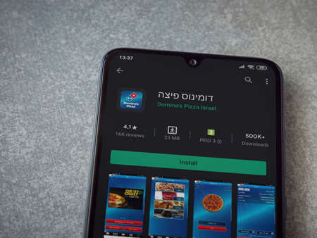 Lod, Israel - July 8, 2020: Domino's Pizza Israel app play store page on the display of a black mobile smartphone on ceramic stone background. Top view flat lay with copy space.