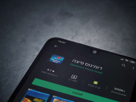 Lod, Israel - July 8, 2020: Domino's Pizza Israel app play store page on the display of a black mobile smartphone on dark marble stone background. Top view flat lay with copy space.