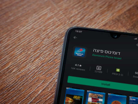 Lod, Israel - July 8, 2020: Domino's Pizza Israel app play store page on the display of a black mobile smartphone on wooden background. Top view flat lay with copy space.