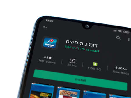 Lod, Israel - July 8, 2020: Domino's Pizza Israel app play store page on the display of a black mobile smartphone isolated on white background. Top view flat lay with copy space. Editorial