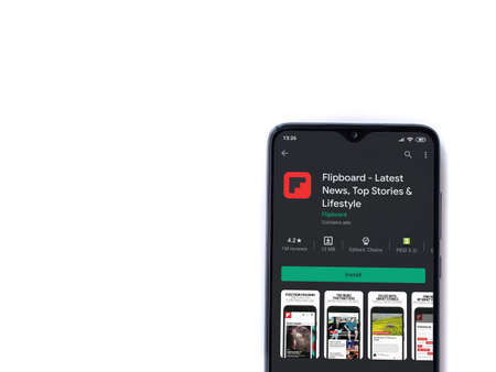 Lod, Israel - July 8, 2020: Flipboard app play store page on the display of a black mobile smartphone isolated on white background. Top view flat lay with copy space.