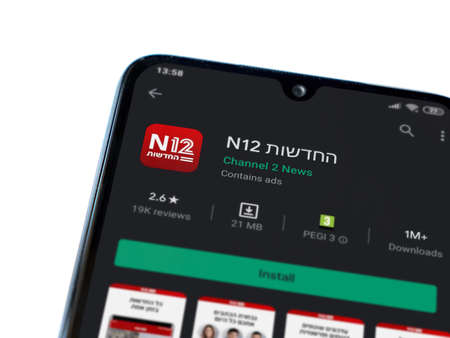 Lod, Israel - July 8, 2020: N12 app play store page on the display of a black mobile smartphone isolated on white background. Top view flat lay with copy space.