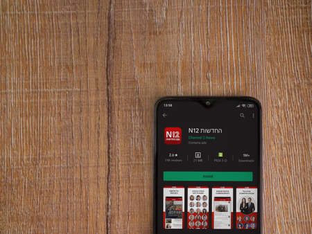 Lod, Israel - July 8, 2020: N12 app play store page on the display of a black mobile smartphone on wooden background. Top view flat lay with copy space. Publikacyjne
