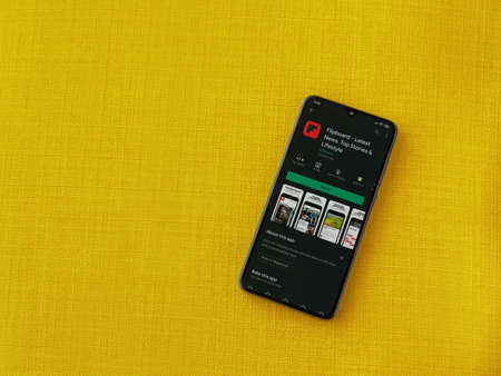 Lod, Israel - July 8, 2020: Flipboard app play store page on the display of a black mobile smartphone on a yellow fabric background. Top view flat lay with copy space. Publikacyjne
