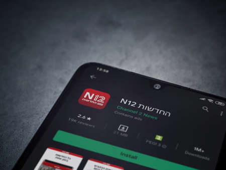 Lod, Israel - July 8, 2020: N12 app play store page on the display of a black mobile smartphone on dark marble stone background. Top view flat lay with copy space. Publikacyjne