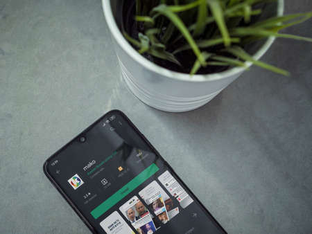 Lod, Israel - July 8, 2020: Modern minimalist office workspace with black mobile smartphone with mako app play store page on marble background. Top view flat lay with copy space.