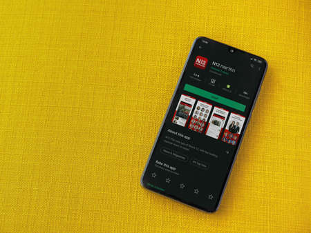 Lod, Israel - July 8, 2020: N12 app play store page on the display of a black mobile smartphone on a yellow fabric background. Top view flat lay with copy space.