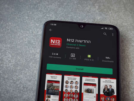 Lod, Israel - July 8, 2020: N12 app play store page on the display of a black mobile smartphone on ceramic stone background. Top view flat lay with copy space. Publikacyjne