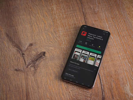 Lod, Israel - July 8, 2020: Flipboard app play store page on the display of a black mobile smartphone on wooden background. Top view flat lay with copy space.