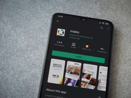 Lod, Israel - July 8, 2020: mako app play store page on the display of a black mobile smartphone on ceramic stone background. Top view flat lay with copy space.
