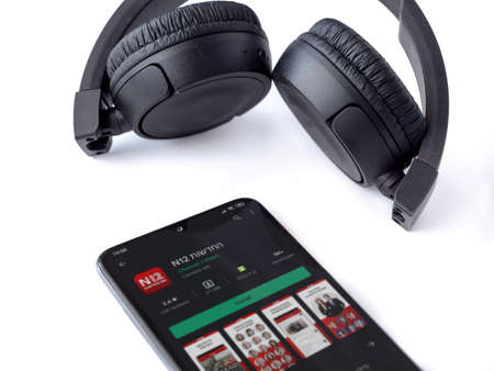 Lod, Israel - July 8, 2020: Black mobile smartphone with N12 app play store page and wireless headphones on a white background. Top view flat lay with copy space.