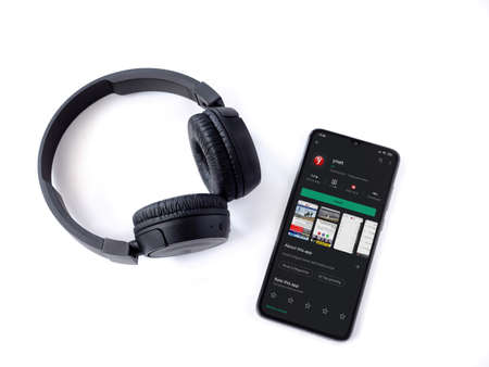 Lod, Israel - July 8, 2020: Black mobile smartphone with ynet app play store page and wireless headphones on a white background. Top view flat lay with copy space.