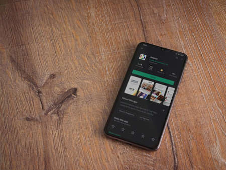 Lod, Israel - July 8, 2020: mako app play store page on the display of a black mobile smartphone on wooden background. Top view flat lay with copy space.