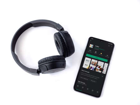Lod, Israel - July 8, 2020: Black mobile smartphone with mako app play store page and wireless headphones on a white background. Top view flat lay with copy space.