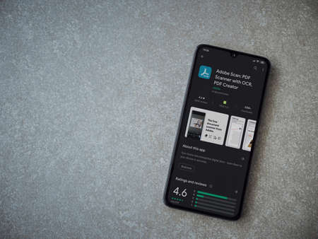 Lod, Israel - July 8, 2020: Adobe Scan app play store page on the display of a black mobile smartphone on ceramic stone background. Top view flat lay with copy space. Editoriali