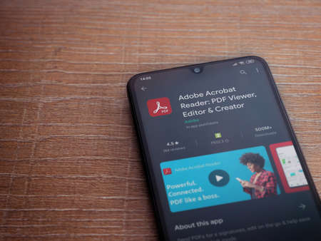 Lod, Israel - July 8, 2020: Adobe Acrobat Reader app play store page on the display of a black mobile smartphone on wooden background. Top view flat lay with copy space.