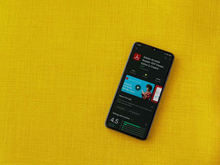 Lod, Israel - July 8, 2020: Adobe Acrobat Reader app play store page on the display of a black mobile smartphone on a yellow fabric background. Top view flat lay with copy space. Editoriali