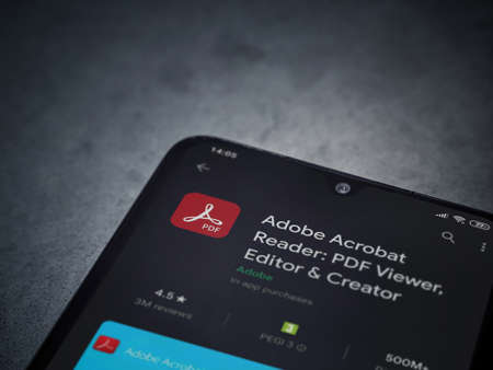 Lod, Israel - July 8, 2020: Adobe Acrobat Reader app play store page on the display of a black mobile smartphone on dark marble stone background. Top view flat lay with copy space.