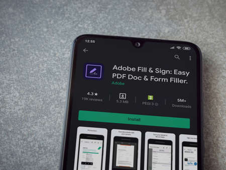 Lod, Israel - July 8, 2020: Adobe Fill & Sign app play store page on the display of a black mobile smartphone on ceramic stone background. Top view flat lay with copy space. Editoriali