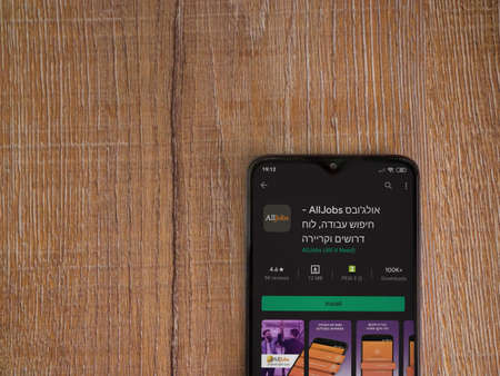 Lod, Israel - July 8, 2020: AllJobs app play store page on the display of a black mobile smartphone on wooden background. Top view flat lay with copy space.