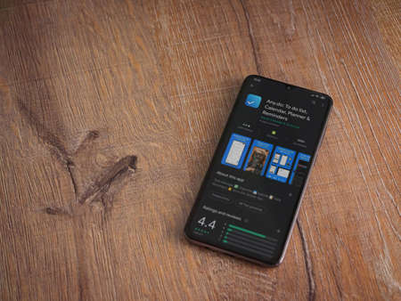 Lod, Israel - July 8, 2020: Any.Do app play store page on the display of a black mobile smartphone on wooden background. Top view flat lay with copy space.