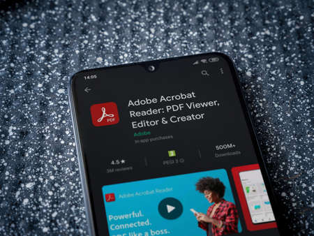 Lod, Israel - July 8, 2020: Adobe Acrobat Reader app play store page on the display of a black mobile smartphone on a metallic background. Close up top view flat lay.
