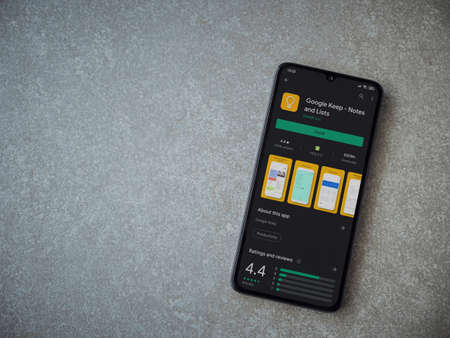 Lod, Israel - July 8, 2020: Google Keep app play store page on the display of a black mobile smartphone on ceramic stone background. Top view flat lay with copy space.