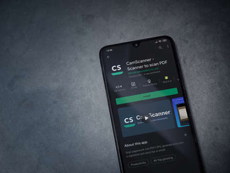 Lod, Israel - July 8, 2020: CamScanner app play store page on the display of a black mobile smartphone on dark marble stone background. Top view flat lay with copy space.