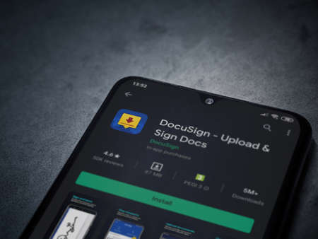 Lod, Israel - July 8, 2020: DocuSign app play store page on the display of a black mobile smartphone on dark marble stone background. Top view flat lay with copy space. Editoriali