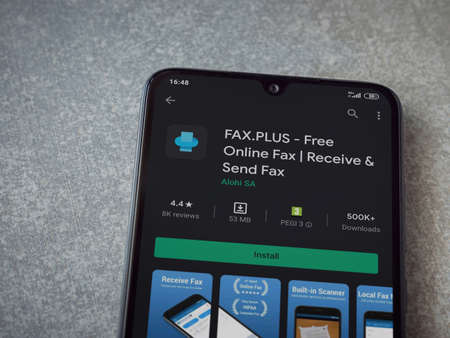 Lod, Israel - July 8, 2020: Fax Plus app play store page on the display of a black mobile smartphone on ceramic stone background. Top view flat lay with copy space.