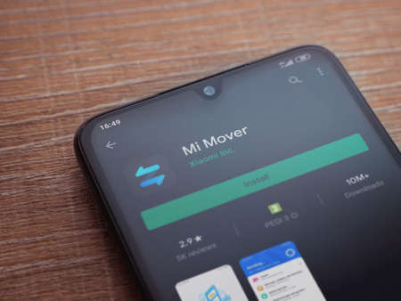 Lod, Israel - July 8, 2020: Mi Mover app play store page on the display of a black mobile smartphone on wooden background. Top view flat lay with copy space.