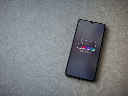 Lod, Israel - July 8, 2020: LG TV Plus app launch screen with logo on the display of a black mobile smartphone on ceramic stone background. Top view flat lay with copy space.