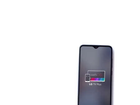 Lod, Israel - July 8, 2020: LG TV Plus app launch screen with logo on the display of a black mobile smartphone isolated on white background. Top view flat lay with copy space.