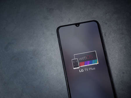 Lod, Israel - July 8, 2020: LG TV Plus app launch screen with logo on the display of a black mobile smartphone on dark marble stone background. Top view flat lay with copy space.