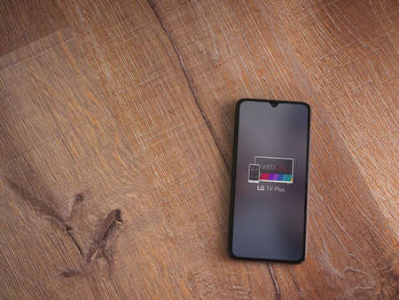 Lod, Israel - July 8, 2020: LG TV Plus app launch screen with logo on the display of a black mobile smartphone on wooden background. Top view flat lay with copy space.