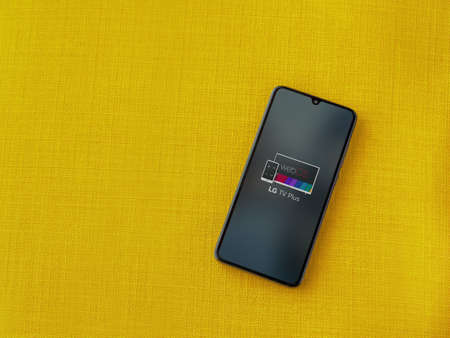 Lod, Israel - July 8, 2020: LG TV Plus app launch screen with logo on the display of a black mobile smartphone on a yellow fabric background. Top view flat lay with copy space.