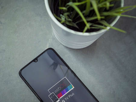 Lod, Israel - July 8, 2020: Modern minimalist office workspace with black mobile smartphone with LG TV Plus app launch screen with logo on a marble background. Close up top view flat lay.