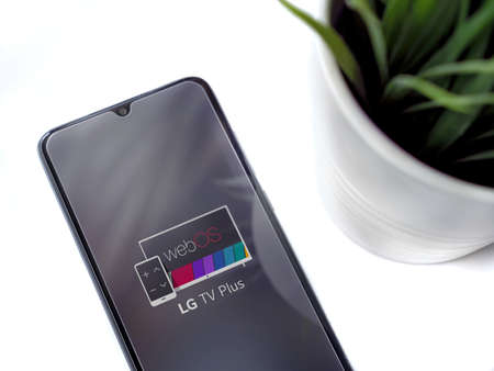 Lod, Israel - July 8, 2020: Modern minimalist office workspace with black mobile smartphone with LG TV Plus app launch screen with logo on a white background. Close up top view flat lay. Editoriali
